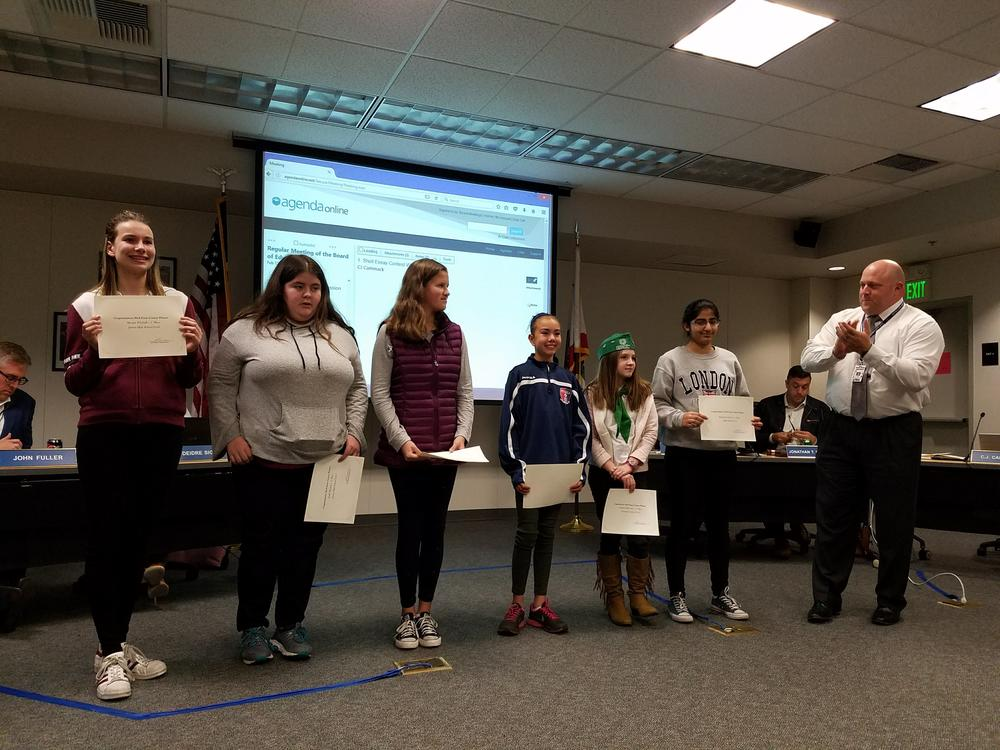 Picture of Superintendent and six students receiving certificates